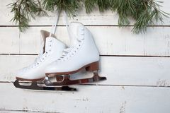 Skates and pine branches on a white wood Stock Photos