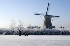 Skating. A photo of a windmill with a blue sky and a frozen river in front stock image