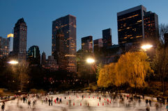 Skating below giants. Ice skaters at Wollman Rink within in Central Park in New York City Stock Images