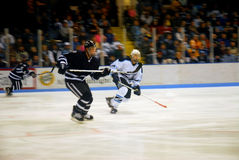 Skating fast. Two college hockey players skating fast across the ice; motion blur Royalty Free Stock Image