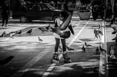 Skating Little Arabic Girl In Central Square. A little Arabic girl skating among pigeons on the central square located in Cinarcik town which is the district of Royalty Free Stock Photo