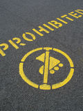 Skating prohibited. A yellow painted pavement sign prohibiting inline skating Stock Photos