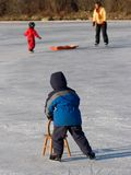 Skating with Support. A young boy uses a chair for support as he skates for the first time in early winter royalty free stock photos