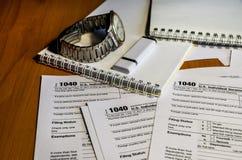 Skatt bildar 1040 anteckningsböcker, klockor och ett pråligt drev på en brun tabell royaltyfria bilder