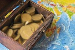 Skattbröstkorgen står på en världskarta mycket av guld- mynt royaltyfri foto