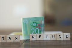 Skatteåterbäring som stavas ut i bokstäver med kontant in bakgrund för kanadensisk dollar Arkivfoto