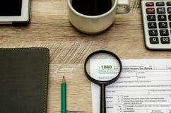 Skattform 1040, ett förstoringsglas Räknemaskin och anteckningsbok ovanför sikt arkivbilder