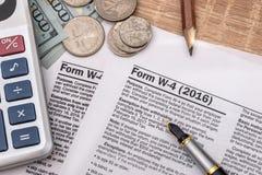 Skattform w4 med pennan och oss dollar, räknemaskin och penna Arkivbild