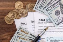 Skattformen för 1040 USA med dolllr fakturerar och mynt Arkivbild