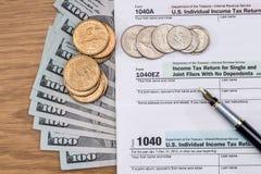 Skattformen för 1040 USA med dolllr fakturerar och mynt Royaltyfri Fotografi
