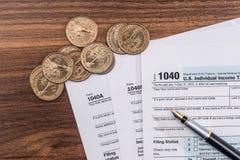 Skattformen för 1040 USA med dolllr fakturerar och mynt Arkivfoto
