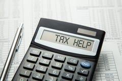 Skatthjälp På skärm av räknemaskinen är skriftlig skatthjälp arkivfoto