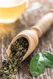 Sked av torkade gröna teblad på trätabellen Royaltyfri Bild