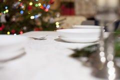 sked med den röda julgranen i bakgrunden, julkottar på den vita tabellinställningen placera text ovanför sikt Royaltyfria Foton