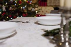 sked med den röda julgranen i bakgrunden, julkottar på den vita tabellinställningen placera text ovanför sikt Arkivfoto