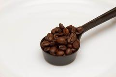 Sked med kaffekorn på en vit bakgrund Arkivfoto