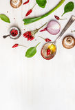 Sked med olja och kryddor och olika vegetariska ingredienser för sunt äta på vit träbakgrund Arkivbild