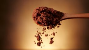Sked mycket av kakaopulver som är tomt på guld- bakgrund arkivfilmer