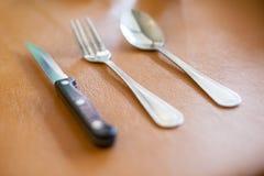 Skeda gaffeln och baktala för äter mat på tabellen Royaltyfri Foto