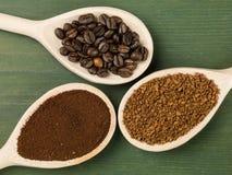 Skedar av ögonblickliga grovkorniga och stekkaffebönor royaltyfria foton