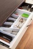 Skedar, gafflar och knivar i bestick boxas enheten Arkivbilder