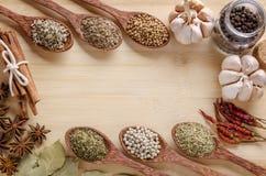 Skedar och kryddor på skärbräda Arkivfoto