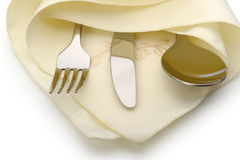 Skeden, gaffeln och en kniv ligger på servett Arkivbild