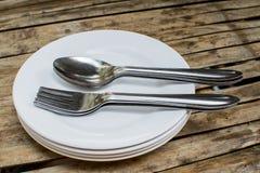 Skedplatta och sked på att äta middag tabellen arkivbilder