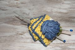 Skein of blue wool with needles on rustic background with copy space royalty free stock image