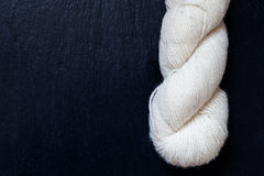 Skein of natural white yarn with black slate Stock Photo