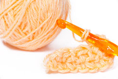 Skein of orange yarn closeup and crocheting. Knitting Stock Images