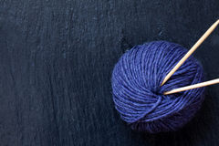 Skein of purple yarn with bamboo knitting needles with black slate background Stock Photos