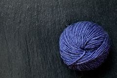Skein of purple yarn with black slate background Stock Images
