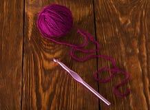 Skein purpurowa wełny przędza i szydełkowy haczyk na ciemnych deskach zdjęcia royalty free