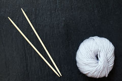 Skein of white yarn with bamboo knitting needles Stock Photo
