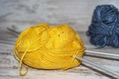 Skeins of blue and yellow wool with needles on rustic background with copy space stock photography
