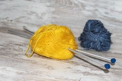 Skeins of blue and yellow wool with needles on rustic background with copy space royalty free stock photography