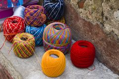 Skeins of bright colored wool lie on the stone border near the wall. In the background are boxes and a coil with a blue ribbon.  stock image