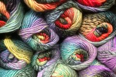 Skeins of knitting wool. Colorful skeins, clews, of thick knitting yarn stacked up on display stock images