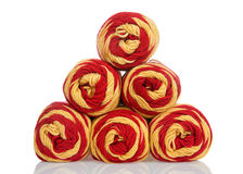 Skeins of red and gold yarn stacked pyramid shape isolated on white Royalty Free Stock Images