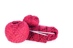 Skeins of red yarn, needles and knitting work Stock Images