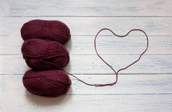 Skeins and thread in the form of heart. Marsala color. Skeins of yarn and thread in the form of heart are in a white vintage wooden desk. Marsala color. Top Stock Image