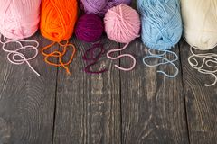 Skeins of yarn assorted colors for needlework on wooden surface. Skeins of yarn assorted colors for needlework on dark wooden surface Royalty Free Stock Photo