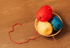 Skeins of yarn in a basket with knitting needles Stock Image