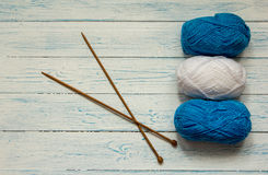 Skeins of yarn and knitting needles are on a white table. Skeins of yarn and knitting needles are located on a white wooden table. Top view Royalty Free Stock Photo