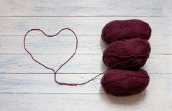 Skeins of yarn are in a white vintage wooden desk. Skeins of yarn and thread in the form of heart are in a white vintage wooden desk. Marsala color. Top view Royalty Free Stock Photos