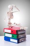 Skelet met stapel van dossiers tegen gradiënt Stock Foto's