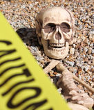 Skeleton Behind Caution Tape. Skeleton in rocks surrounded by yellow caution tape stock images