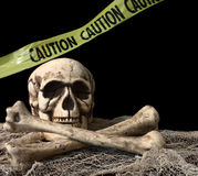 Skeleton on Black Background. Skull and bones with caution tape in the back stock photos