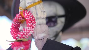 Skeleton in Black Hat and Sunglasses Praying Hands Folded. Statue for Dia De Los Muertos Mexican Holiday. 4K. Skeleton in Black Hat and Sunglasses Praying Hands stock video
